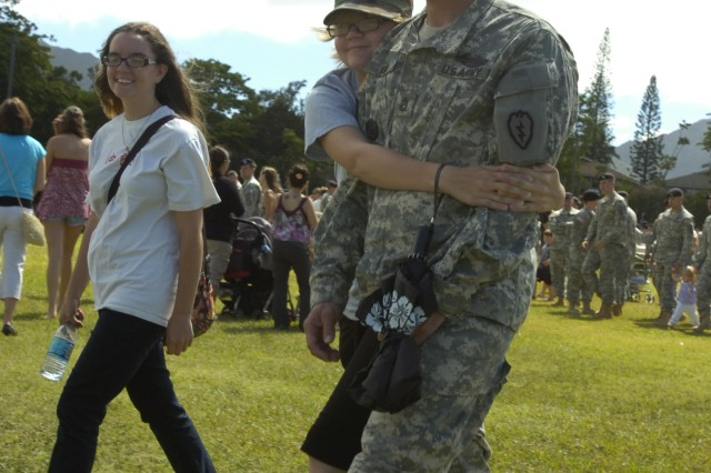 Sergeant 1st Class David Kirby, Company C., 1st Battalion, 21st Infantry Regiment, 2nd Brigade Combat Team, attempts to walk as his daughter, Kylee Kirby, embraces him in an affectionate hug following the brigade's deployment ceremony held at Sills Field on Schofield Barracks, Hawaii, June 24. Kirby is one of many Soldiers enjoying his last few days with family members before deploying with his unit to northern Iraq for 12 months. (U.S. Army photo by Spc. Jesus J. Aranda, 25th Infantry Division Public Affairs Office)