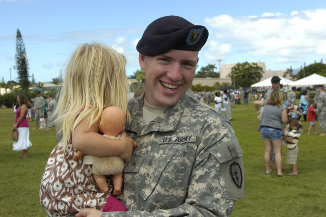 A Soldier serving with Headquarters and Headquarters Company, 2nd Brigade Combat Team, 25th Infantry Division cradles his daughter following the brigade's deployment ceremony held at Sills Field on Schofield Barracks, Hawaii, June 24. The brigade will be deployed to the northern Iraq region for 12-months as they serve in an advise and assist role alongside Iraqi military and government leaders. (U.S. Army photo by Spc. Jesus J. Aranda, 25th Infantry Division Public Affairs Office)