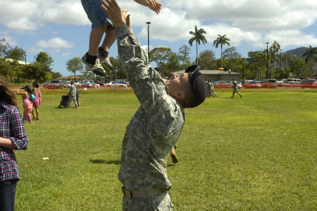 Sergeant Michael Johnson, a fire support sergeant with Headquarters and Headquarters Company, 2nd Brigade Combat Team, 25th Infantry Division, playfully tosses his son, Hunter Johnson, up into the air following the brigade's deployment ceremony held at Sills Field on Schofield Barracks, Hawaii, June 24. Kirby is one of many Soldiers enjoying his last few days with family members before deploying with his unit to northern Iraq for 12 months. (U.S. Army photo by Spc. Jesus J. Aranda, 25th Infantry Division Public Affairs Office)