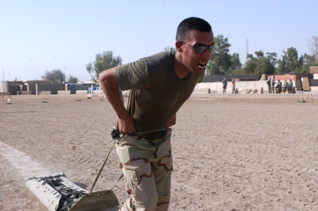 Sgt. 1st Class Ali Maji, an NCO with the 8th Division, Iraqi Army drags 180 Lbs. of weight behind him to end the physical fitness portion of the United States Division - South Soldier of the Quarter Competition on Contingency Operating Site Echo June 18. The event brought U.S. and Iraqi Forces together in competition for the title of best Soldier and NCO of the Quarter.