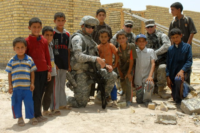 Spc. Ricardo Mireles, a psychological operations specialist with the 341st Tactical Psychological Operations Company, 17th Psychological Operations Group and native of San Antonio, , poses for a photo with some local children in front of a school construction site in the Bani Samala area June 14. The school will serve about 400 children, almost 300 more than the current school.