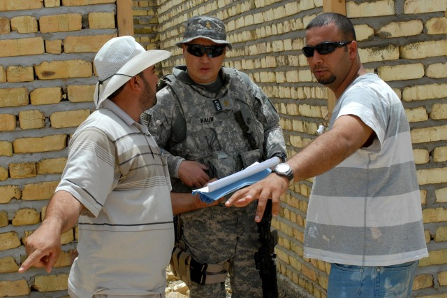 Maj. Joseph Hauw, the civil liaison team officer in charge with the 358th Civil Affairs Brigade and native of Riverside, Calif., , discusses the progress on a school being built on site in the Bani Samala area June 14. The current school has to hold some classes due to its diminished capabilities.