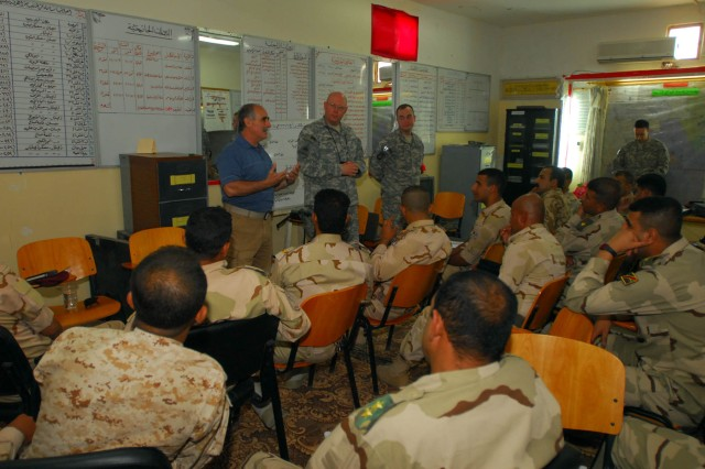 A translator with the 3/3 STT, Sgt. 1st Class Dean Crist, the brigade communications noncommissioned officer-in-charge, and Pfc. Alex Elliot of the 412th Aviation Support Battalion, give a class on basic communications methods to officers with the 10th Iraqi Army Division at Contingency Operating Station GarryOwen, Iraq, June 3.