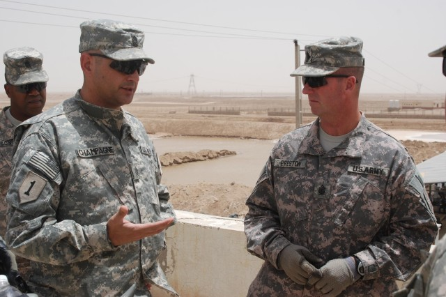 Command Sgt. Maj. Jim Champagne, left, the senior noncommissioned officer of United States Division-South and the 1st Infantry Division, talks to Sgt. Maj. of the Army Kenneth Preston, senior enlisted member of the U.S. Army, at the Shalamcha Point of Entry in southern Iraq June 25. Shalamcha is positioned on the Iraq-Iran border and is a critical part of smuggling interdiction in southern Iraq.