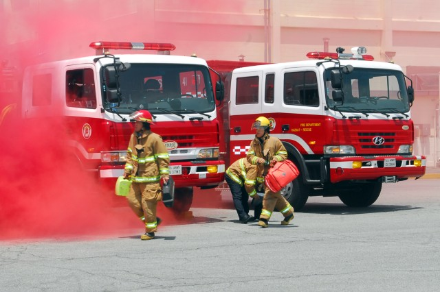 Local Busan firefighters arrive to assist in caring for victims at the scene where smoke is in the air during an exercise May 20.