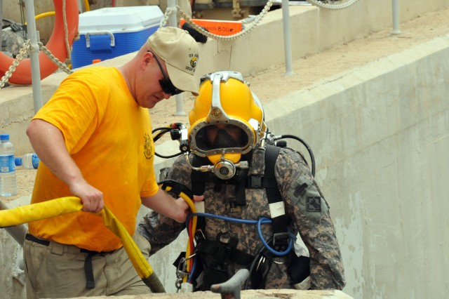 KUWAIT NAVAL BASE, KUWAIT-Capt. Edouard De Courreges, detachment cmdr for the 511th Engineer Dive Team, is assisted up the steps at the Kuwait Naval Base, Kuwait, port wall after being promoted to the rank of Capt. in an underwater promotion ceremony 40 feet beneath the surface.