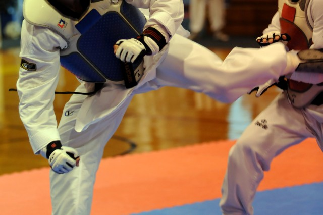 U.S. Army World Class Athlete Program martial artist Staff Sgt. Jonathan Fennell of Fort Carson, Colo., scores with a kick to the chest of Air Force Capt. Ascenzo Bonitati of Pensacola, Fla., en route to a 6-2 victory in the lightweight division of the 2010 Armed Forces Taekwondo Championships on June 19 at Fort Indiantown Gap, Pa.