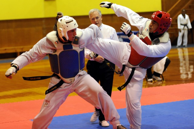 Army World Class Athlete Program martial artist Capt. Alexander White (right) kicks for the head of All-Air Force Sgt. Brian Biviano en route to a 5-2 victory in a middleweight bout at the 2010 Armed Forces Taekwondo Championships, June 19 in Fort Indiantown Gap, Pa.