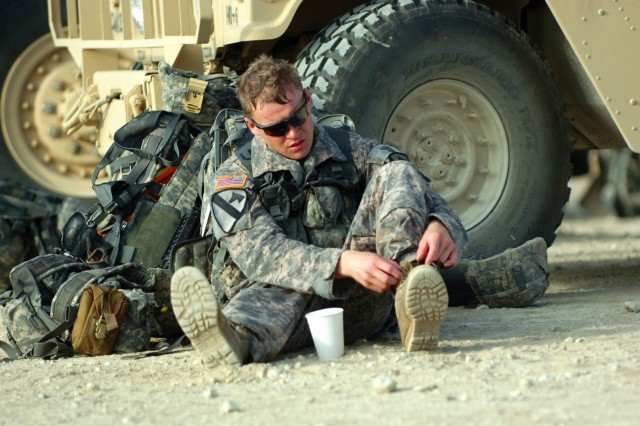 FORT HOOD, Texas - Spc. Jeffrey Miller, of Standish, Mich., a forward observer with 2nd Battalion, 8th Cavalry Regiment, 1st Brigade Combat Team, 1st Cavalry Division, loosens his boots, June 25, after completing a 12 mile road march in two hours, 57 minutes. The road march was the final task in the 1st BCT Iron Warrior Stakes competition.