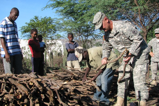 Col. Michael Borrel, Task Force Kout Men commander, helps a Gel Petil, a charcoal maker in Madrin, Haiti stack wood which will be smoked into charcoal for families in the area around the New Horizons-Haiti 2010 encampment to use as cooking fuel. (U.S. Army Photo by Maj. Scott Bell, TF Kout Men PAO/RELEASED)