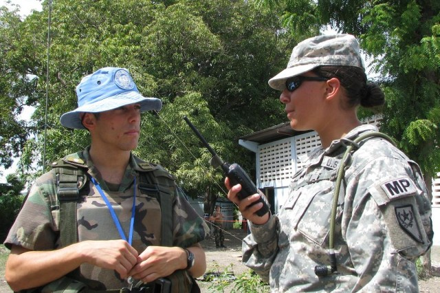 Nevada National Guard Pfc. Patricia Arnold, a member of the 485th Military Police Co., coordinates with Argentina 2nd Lt. Francisco Moulia, whose MINUSTAH troops provide security for the Govt. of Haiti at a medical readiness exercise at the Les Poteau clinic site near Gonaives, Haiti. (U.S. Army Photo by Maj. Scott Bell, Task Force Kout Men PAO/RELEASED)