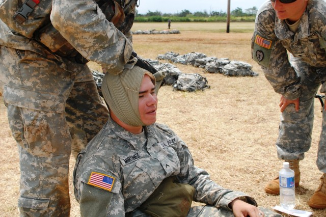 A Soldier of 3rd Brigade Combat Team, 25th Infantry Division properly wraps a fellow Soldier's head with a bandage to showcase his proficiency on treating a wounded casualty during the Bronco Brigade's Warrior Task Training held from June 20-25 at Schofield Barracks, Hawaii.
