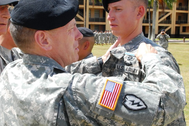 Maj. Gen. Bernard S. Champoux, commanding general, 25th Infantry Division, pins the Expert Infantry Badge on a 2nd Lieutenant during the 3rd Brigade Combat Team's EIB pinning ceremony, held June 25 at Schofield Barracks, Hawaii.