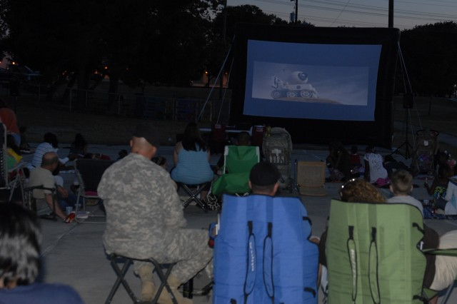 "FORT HOOD, Texas- Comanche I and II residents sit on blankets and lawn chairs to watch ""Planet 51"",June 26, during ""Movie on the Lawn with Dad"" night behind Comanche II's Community Life Building on Fort Hood. The event was sponsored by Fort Hood's United Service Organizations and Comanche Community Life Center."