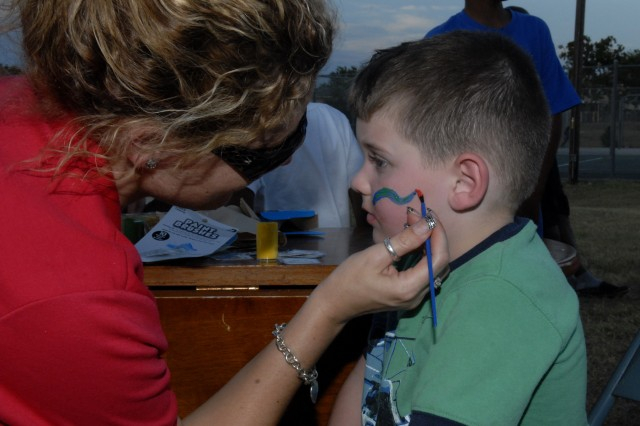"FORT HOOD, Texas- Nicole Johnson, a resident service coordinator for Comanche Housing Areas I and II paints a snake on Timothy St. John's face, June 26, during ""Movie on the Lawn with Dad"" night behind Comanche II's Community Life"