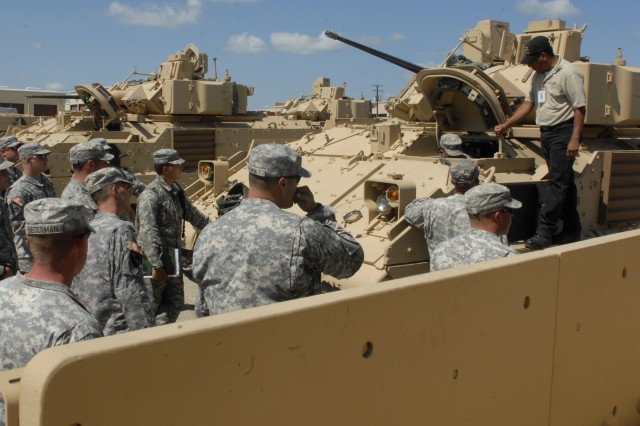 FORT HOOD, Texas-Troopers from 6th Squadron, 9th Cavalry Regiment, 3rd Brigade Combat Team, 1st Cavalry Division crowd around a Bradley Fighting Vehicle as Chris Gonzales, an instructor from BAE Systems explains the procedures for jump-starting a vehicle, during sustainment training, June 25, at the squadron's motor pool.