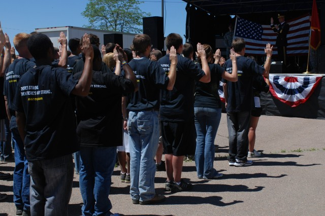 FORT CARSON, Colo.---More than 80 future Soldiers and 20 re-enlisting Army recruiters raise their right hands to recite the oath of enlistment during a new recruit ceremony June 19 at Iron Horse Park.