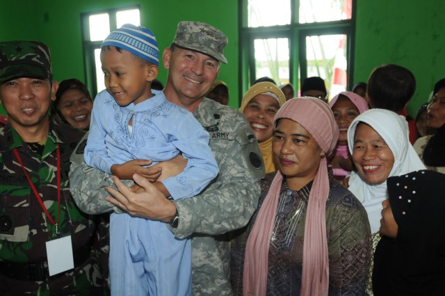 BANDUNG, Indonesia--Commander, U.S. Army, Pacific, Lt. Gen. Benjamin R. Mixon holds a young child while attending the opening of a baby care clinic with Indonesian Brig. Gen. Bachtiar S.IP. (left).