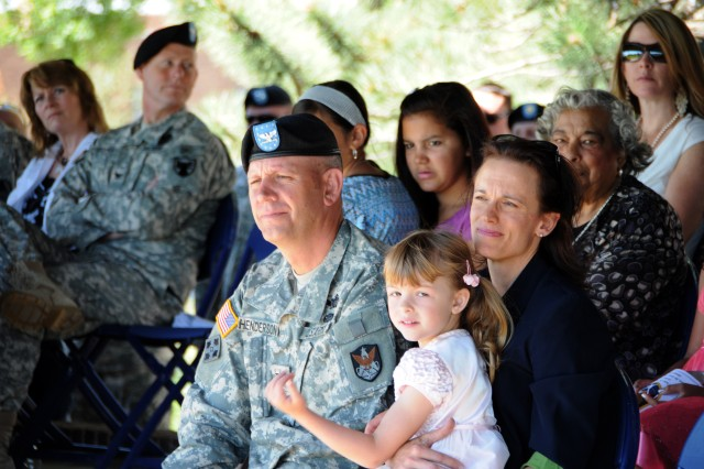 Incoming 1st Space Brigade Commander, Col. Eric Henderson, his wife Jean and their daughter listen to remarks from Lt. Gen. Kevin T. Campbell.