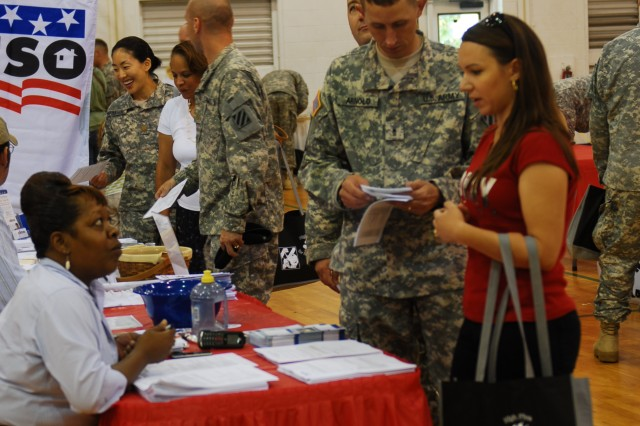 Warrant Officer Dwayne Arnold, HHC, 4th IBCT, 3rd ID reviews a pamphlet as his wife, Danijela, speaks with Balfour Beatty leasing specialist Macie Nicholsen, during the ACS-sponsored Soldier and Family Pre-Deployment Fair at Fort Stewart, June 24.