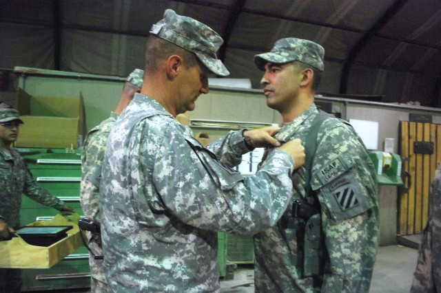 Chief Warrant Officer  Rick Campbell, a pilot in Task Force Knighthawk, 3rd Combat Aviation Brigade, TF Falcon, from Havertown, Pa., receives a Combat Action Badge at Bagram Airfield, June 26.