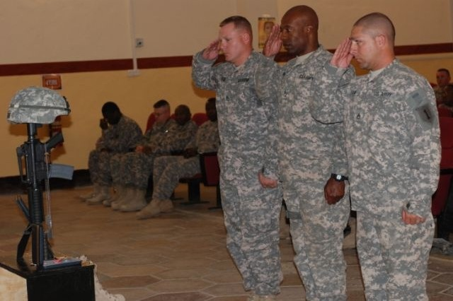 Team Kahuna members pay their respects to fellow team member Capt. Joy Gapuzan, 1/10 FA, 3rd HBCT, during a memorial service held in his honor at COB Delta, June 4. Captain Gupuzan, the team's logistics officer for the past year, died while on leave during his third combat tour.