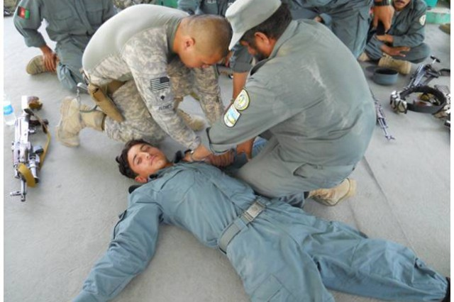 KHOST PROVINCE, Afghanistan - U.S. Army Spc. Paolo Flores, from San Diego, provincial headquarters squad medic, 330th Military Police Company, instructs Afghan Uniformed Policemen at the Khost Provincial Headquarters on how to provide tactical casualty care and first aid, June 27. Soldiers from 330th Military Police Company, 95th MP Battalion, Task Force Sheriff, lead the two-day course, which taught law enforcement skills including basic weapons handling, safety, combat casualty care and first aid.