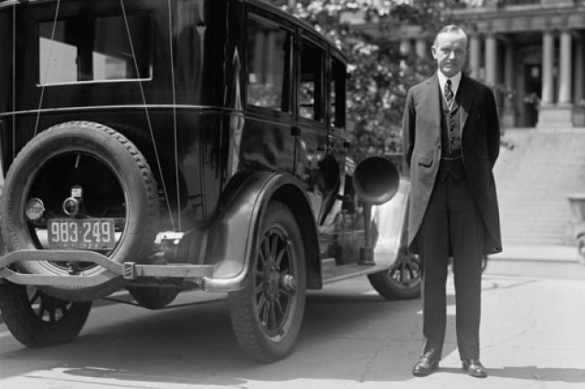 President Calvin Coolidge stands next to a presidential fleet vehicle. At one time, Soldiers served as drivers for the president.