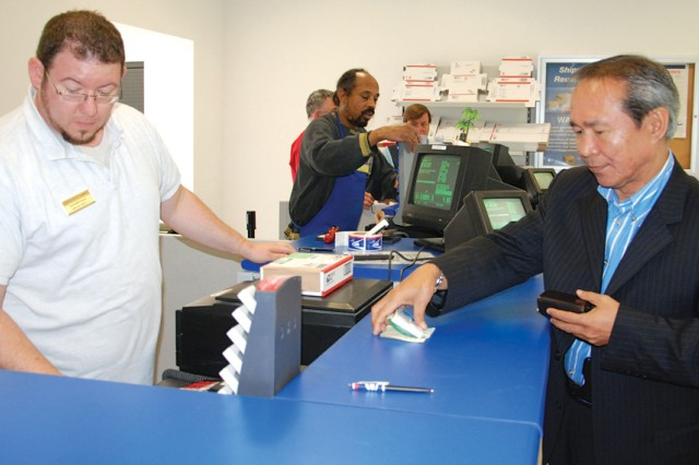 """Aaron Grimes, mail clerk, helps the first customer at the Kelley Barracks Postal Service Center, Ishmael Mama, following the ribbon cutting ceremony June 14. The PCS is a """"one-stop shop"""" offering consolidated postal operations."""