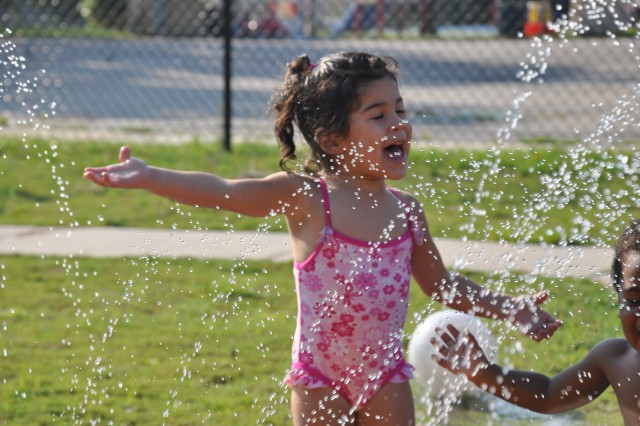 Milynn Cordaro, 2, tries to catch a few drops of water in her mouth as she plays in the sprinklers with classmates last week at the Scales Child Development Center.
