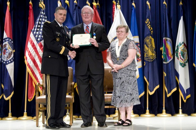 Lt. Gen. William Phillips, former Picatinny commanding general and the Army's current principal military deputy to the assistant secretary of the Army for acquisition, logistics and technology, presents outgoing Armament Research Development and Engineering Center Director Dr. Joseph A. Lannon with a retirement certificate, while Lannon's wife Elizabeth looks on.