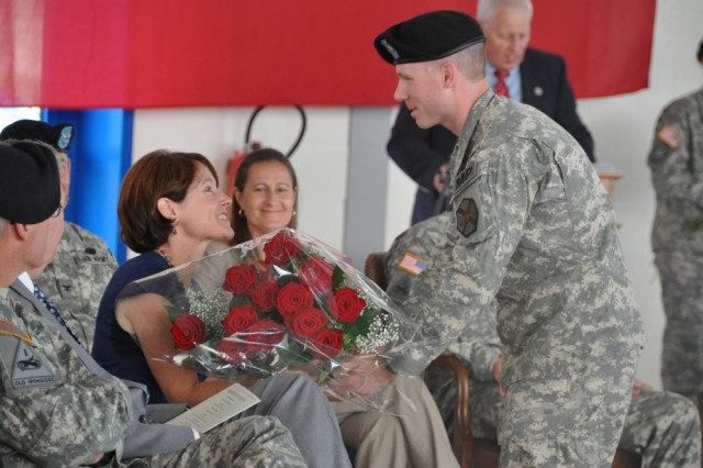 CHIEVRES, Belgium - U.S. Army Garrison Benelux noncommissioned officer of the year Sgt. Jeremiah Sutton presents flowers to Laure Drago, wife of outgoing Benelux commander Col. James Drago at the change of command ceremony on the air base here June 30.