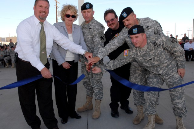 "Fort Irwin and National Training Center Commander Brig. Gen. Robert ""Abe"" Abrams, center, leads a ribbon cutting ceremony that commemorated new emergency services capabilities at Fort Irwin, June 29."""