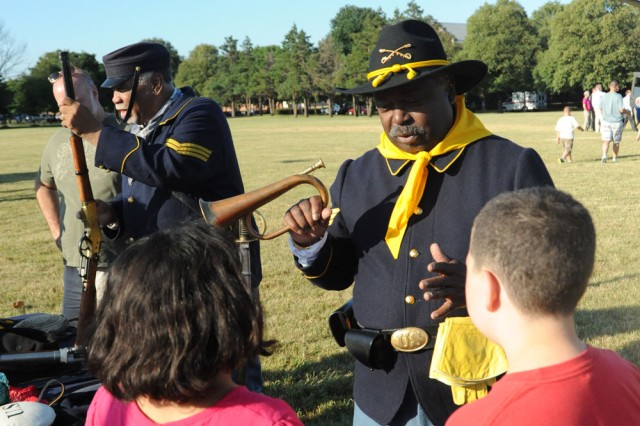"""Trooper Chester Moody, a member of the 9th and 10th (Horse) Calvary, """"The Buffalo Soldiers,"""" The Oficial Army Unit Association, The Greater Washington Chapter, talks with school students about the bugle."""
