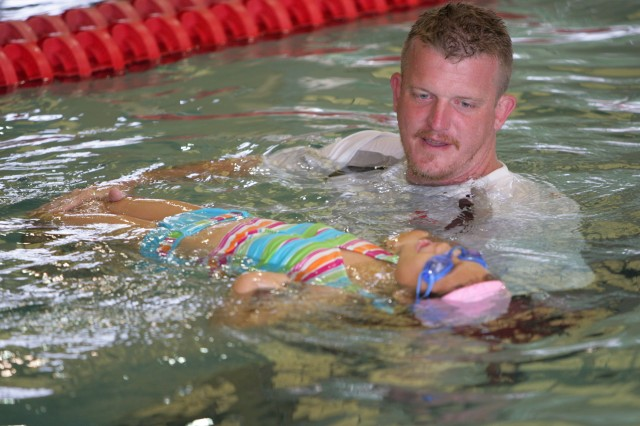 Jason Browning, water safety instructor and aquatics assistant manager, teaches elementary backstroke movements to Tiara Clapper, daughter of Mijung and Staff Sgt. Larry Clapper, C Company, 434th Field Artillery Detachment. Browning recently prevented a possible drowning at Rinehart Fitness Center pool at Fort Sill, Olka. when he rescued a child floundering in the water.