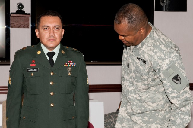 U.S Army Research, Development and Engineering Command Sgt. Maj. Hector Marin, right, gives Sgt. Julio Castellanos close scrutiny during his appearance before the Soldier of the Year board July 1.