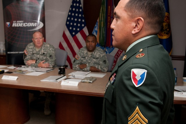 Board members Sgt. Maj. William Tager and Command Sgt. Maj. Hector Marin watch as Sgt. Julio Castellanos performs facing movements for the U.S. Army Research, Development and Engineering Command Soldier of the Year board.