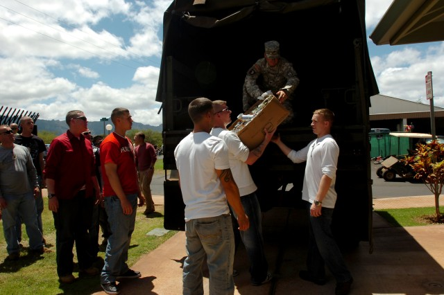 """Soldiers and officers of the 25th Infantry Division help unload non-perishable foods during the """"Freedom Ride"""", the division's motorcycle mentorship program, June 30, at the Kahikolu 'Ohana Hale 'O Wai'anae homeless shelter, Waianae, Hawaii. """"The inspiration really is a way to give back during the holiday. People were more than willing to give what they could,"""" said Sgt. 1st Class Robert J. Martin."""