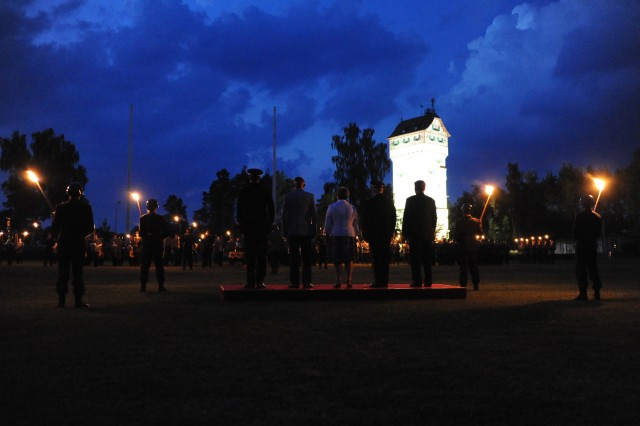 Senior members of the German government and military, alongside senior American military officials, face the historic Grafenwoehr Tower, illuminated in the background, as they stand in review of German Soldiers during the Grosse Zapfenstreich, or military tattoo. The June 30 ceremony, commemorating the 100th Anniversary of the Grafenwoehr Training Area, is the highest honor German Federal Armed Forces can render.