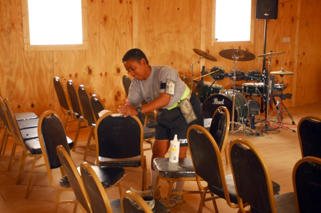 Staff Sgt. Evvere Anthony, a native of Glendale, Az., and the chaplain noncommissioned officer-in-charge for 2nd Battalion, 285th Aviation Regiment, Task Force 12, helps set-up the last of the chairs June 24 in the new Victory Chapel as part of getting it ready for its July 1dedication at Contingency Operating Base Adder, Iraq.