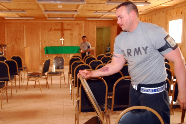 Spc. Ryan Emerson, the chaplain assistant for 2nd Battalion, 285th Aviation Regiment, Task Force 12, who hails from Long Beach, Calif., but now calls Katterbach, Germany, home, helps set-up and clean the last of the chairs June 24 in the new Victory Chapel as part of getting it ready for its July 1 dedication  1 at Contingency Operating Base Adder, Iraq.