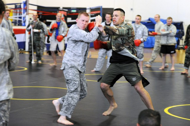 PRESIDIO OF MONTEREY, Calif. - Spc. Anthony DeBerry, Co. B, 229th Military Intelligence Battalion, endures punches from Presidio of Monterey Combatives instructor Sgt. 1st Class James Fortier during his clinch drill.