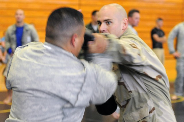 """PRESIDIO OF MONTEREY, Calif. - Capt. Christopher Green, Co. B, 229th Military Intelligence Battalion company commander, tests Sgt. 1st Class Juan Munoz, Presidio of Monterey career counselor, during a clinch drill at the Prrice Fitness Center here June 12. """"I always say, the first time a person is punched hard in the face is a truly self-enlightening experience, You learn a lot about yourself in that split second,"""" said Green"""