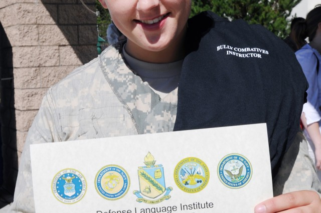 PRESIDIO OF MONTEREY, Calif. - Pfc. Leslie Steele, Co. B, 229th Military Intelligence Battalion, proudly displays her Modern Army Combatives Program Level I certificate and instructor t-shirt after completing 40 hours of instruction June 12. Steele went four rounds of clinching with four wins and suffering a momentary knockout to earn her certification.
