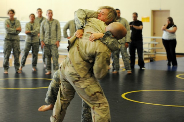 """PRESIDIO OF MONTEREY, Calif. - Pfc. Leslie Steele tries to clinch the bigger, stronger Capt. Christopher Green during a fourth round of clinch drills for her Combatives certification. """"I told Steele she did not have to do the 4th round, but if she did I was going to push her. She said to me that she didn't yet feel she was pushed to the limit. She missed her flight home to stay for the clinch and she said she wanted to feel she 'earned it,' I promise, she and (the rest of her class) earned it,"""" said Green."""