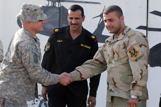 BAGHDAD - Lt. Col. Andrew Danwin (left), commander of 307th Brigade Support Battalion, 1st Advise and Assist Brigade, 82nd Airborne Division, United States Division - Center shakes the hand of an Iraqi soldier at Al Asad Air Base June 20 after delivering two Low Cost, Low Altitude Aerial Resupply System bundles. The system will enable Iraqi Army soldiers to rapidly deploy items such as ammunition, water and food to soldiers outside of their bases. (U.S. Army photo by Sgt. Phillip Valentine, 366th MPAD, USD-C)