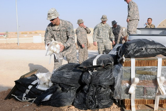 BAGHDAD - Capt. Kyle Brown, assistant operations officer and a Manhattan Beach, Calif., native assigned to 307th Brigade Support Battalion, 1st Advise and Assist Brigade, 82nd Airborne Division, United States Division - Center, helps fellow 307th Soldiers unload extra equipment that will be used to assemble future Low Cost, Low Altitude Aerial Resupply System bundles at Al Asad Air Base, June 20. The system is used to deliver small, essential items to Soldiers in the field for rapid resupply. (U.S. Army photo by Sgt. Phillip Valentine, 366th MPAD, USD-C)