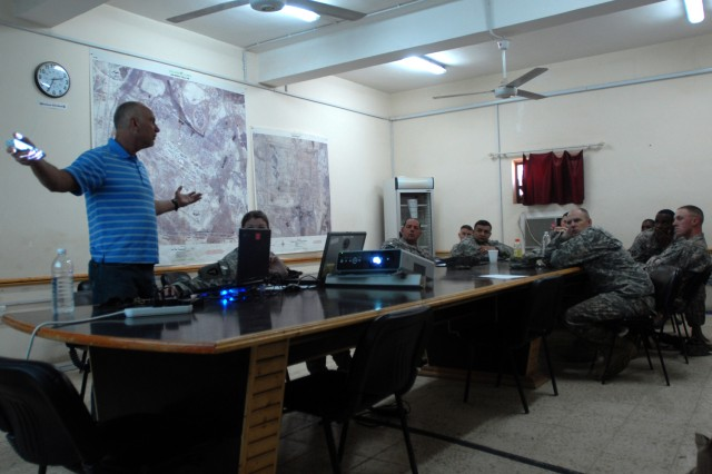 Larry Wise, a retired Army command sergeant major working as a field service engineer for Tapestry Solutions, talks with Army logisticians about the Logistics Reporting Tool during a workgroup meeting at Contingency Operating Base Adder, Iraq.