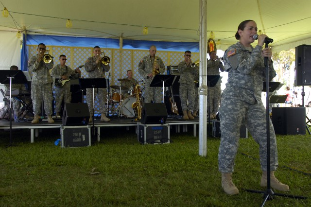 """Specialist Chelsea Gonzalez performs lead vocals during a performance by members of the Tropic Lightning Band's """"Attitude"""" esemble perform for a crowd of guests on Sills Field during the during the 39th Annual 4th of July Spectacular at Schofield Barracks, Hawaii, July 4. The public event invited families to the many games, prize giveaways and performances in celebration of Independence Day. (U.S. Army photo by Spc. Jesus J. Aranda, 25th Infantry Division Public Affairs Office)"""