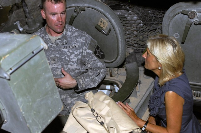 Sgt. Jed Glover, a vehicle commander for Headquarters Company, 4th Stryker Brigade Combat Team, 2nd Infantry Division, explains some of the features of the Stryker combat vehicle to Dr. Jill Biden, wife of Vice President Joe Biden, during a 4th of July visit to the brigade.